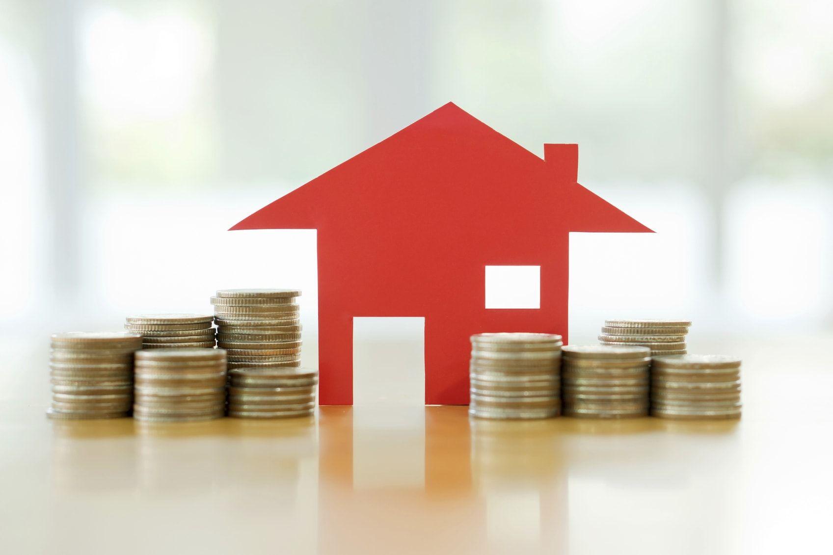 monedas y casa papel representando el gasto de las viviendas