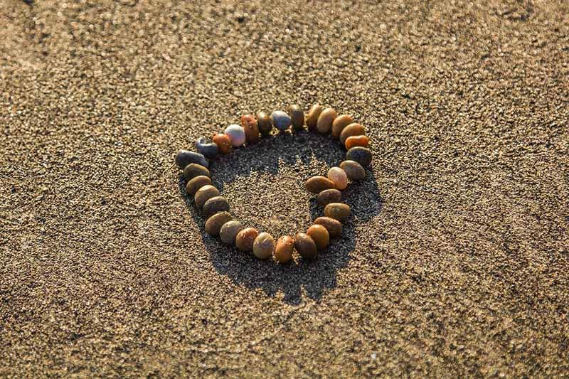arena de la playa en septiembre con corazón de piedras