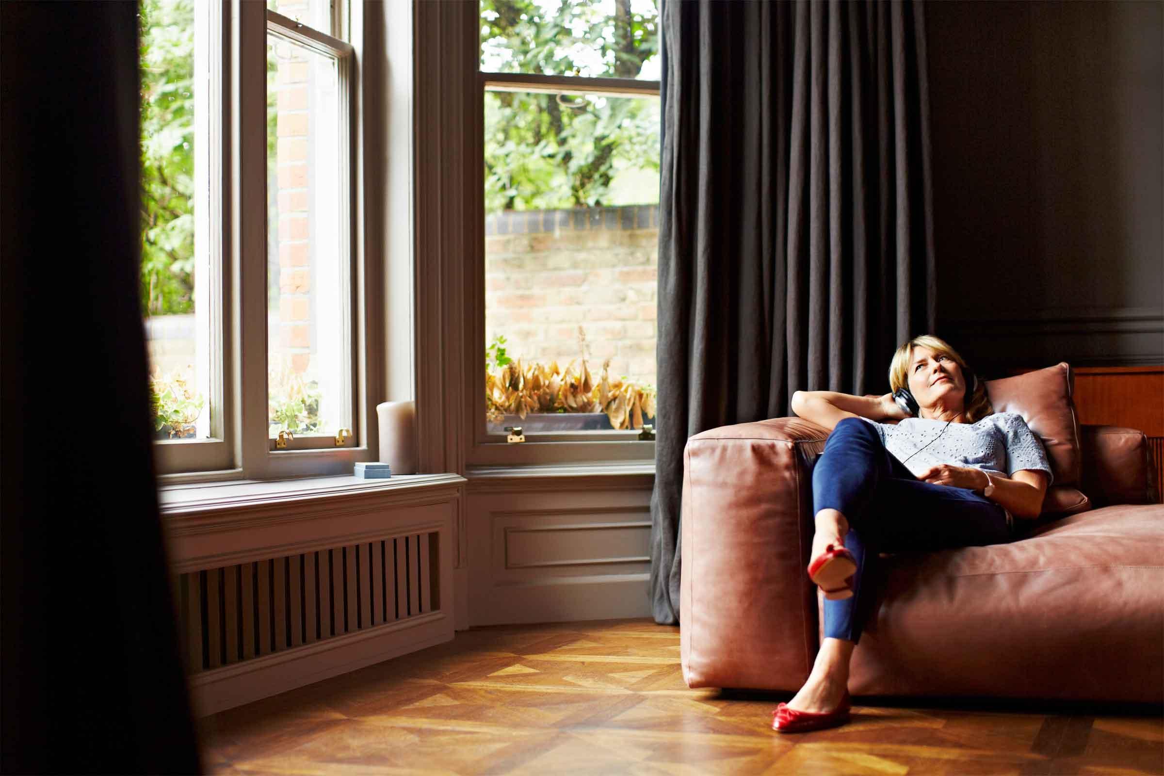 Mujer en un sofá dentro de su casa escuchando música despreocupada