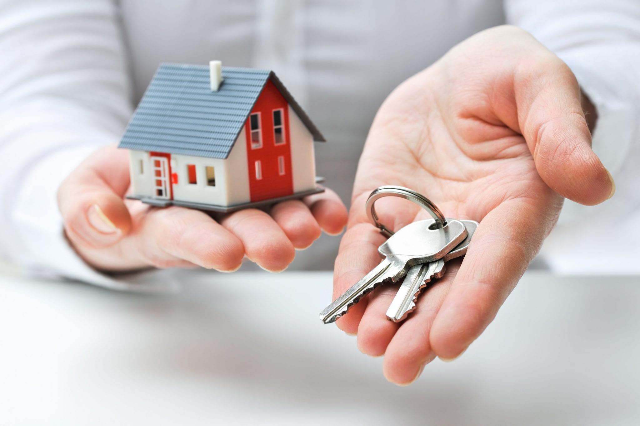 llaves en una mano y una casa
