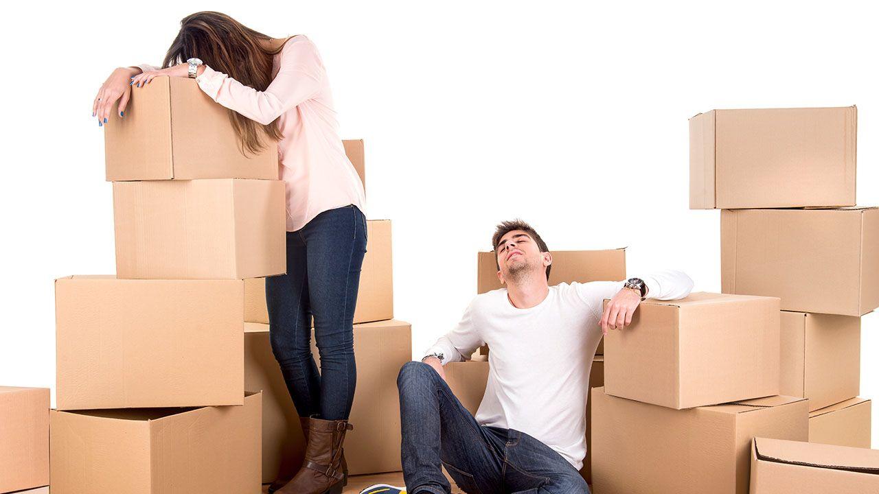Una pareja encima de unas cajas de mudanza