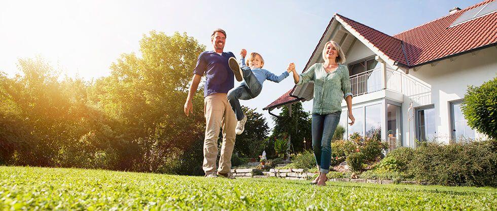 Una familia feliz con una casa de fondo