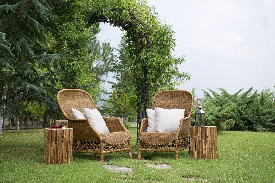 Jardín con dos preciosas sillas de mimbre con cojines blancos