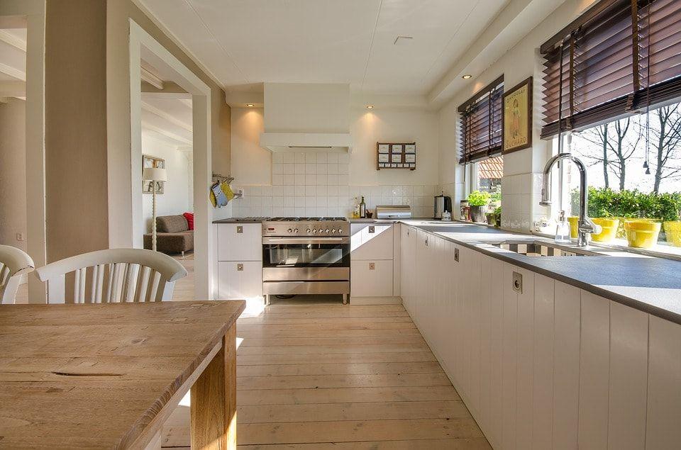 Cocina en tonos blanco, madera, con decoración de plantas con macetero en amarillo.
