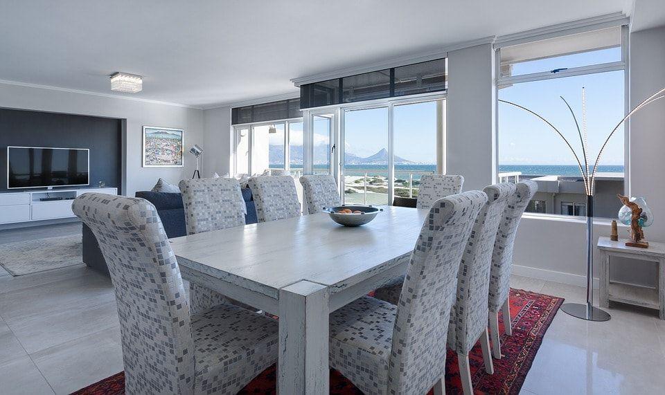 Salón decorado en tonos fríos con cristalera con vistas al mar y la montaña