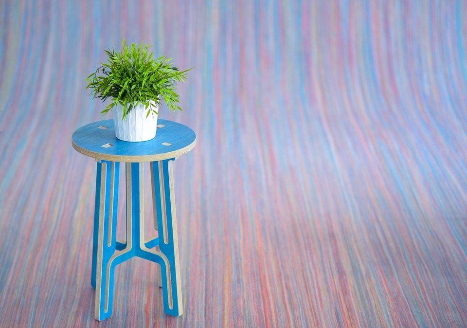 Taburete pintado en azul con planta encima